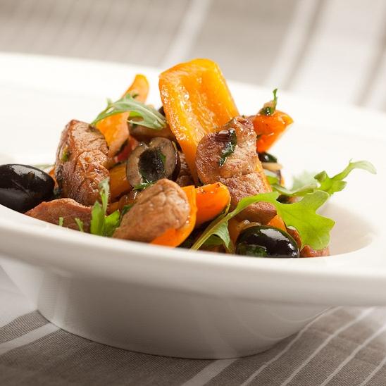 Zoetzure roerbak van Snackpaprika, sinaasappelsap, varkenshaas met rucolasla en olijfjes.